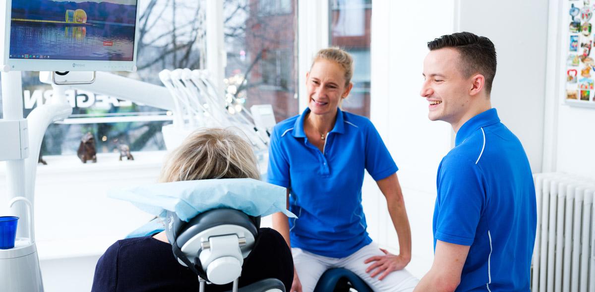 Tandlæge Jacob og klinikassistent Lotte sidder sammen med en patient