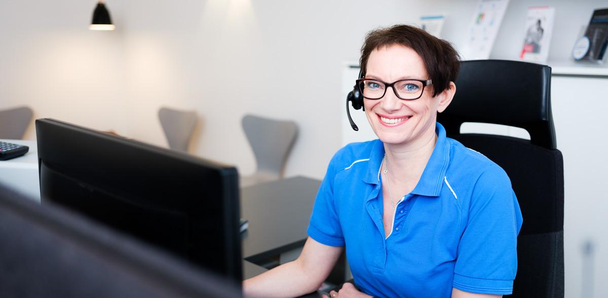 Klinikadministrator Tine sidder ved computeren og snakker i telefon